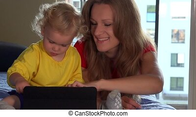 Cute toddler girl and her mom smile using tablet computer...