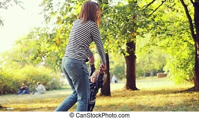 Mother and son having a great weekend in the autumn park in...