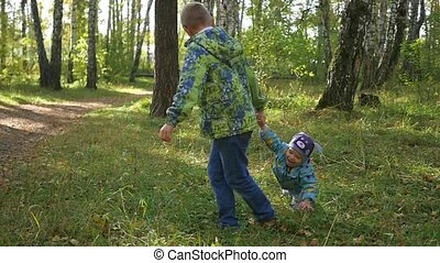 the child plays with his younger brother in the Park in...