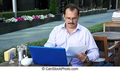 Middle age businessman works on laptop and talking on a...