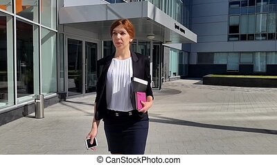 Young business woman walking to the office early