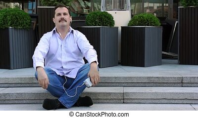 Middle age businessman listen music from smartphone sitting...