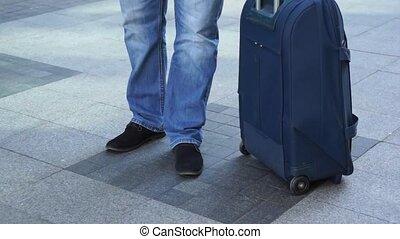 Waiting concept. Legs around suitcase