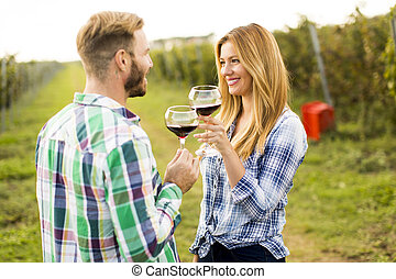 Wine tasting in the vineyard - Young happy couple holding...