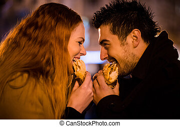 Couple duel - eating together in street