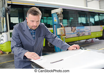 Man in bus garage cleaning panel