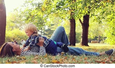 Beautiful mom and cute kid falling down on the grass in autumn park, happy family in nature concept in slowmotion. 1920x1080