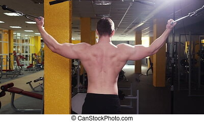 The man trains biceps in the gym