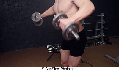 A man with a dumbbell in the gym bodybuilding