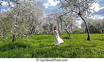 Young woman having fun in the blooming apple garden