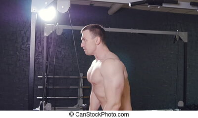 man exercising in trainer for triceps muscles in the gym -...