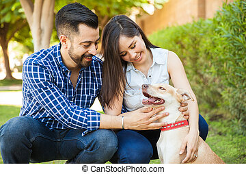 Young couple petting their dog - Attractive young couple...