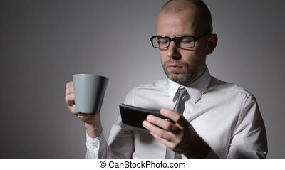 elegant businessman in white shirt holding a cup of coffee...