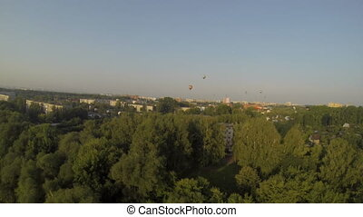 Top view of hot air balloons and city in summer time