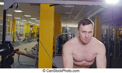 The man trains biceps in the gym - Man at the gym. Man makes...