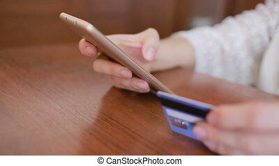 woman makes a purchase using a smartphone and a bank card....