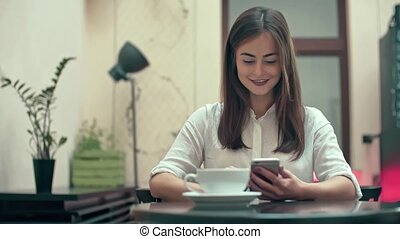 Woman Using App on Smartphone in Cafe - Woman using app on...