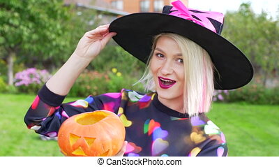 Young woman wearing witch hat and with jack latern on...