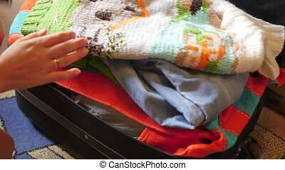 she tries to zip up a suitcase full of stuff - Woman trying...