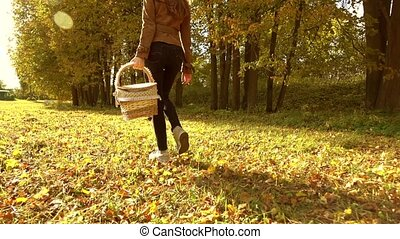 Brunette woman walking through autumn forest holding a...