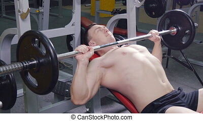 Young man bench pressing weights at a gym, side view...