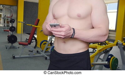 man uses fitness tracker in the gym - Young man uses fitness...