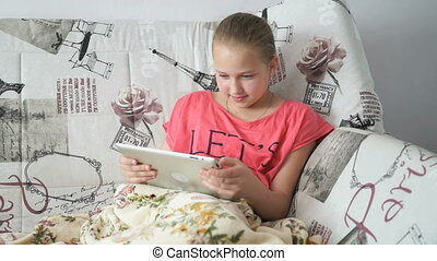 Teenager girl uses a digital tablet on the bed - A smiling...
