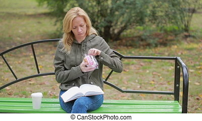 blond girl in a park eating a donut. Woman outdoors chews...