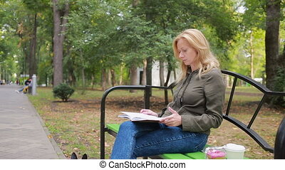 blonde Woman Reading Book on Brench in Autumn Park.