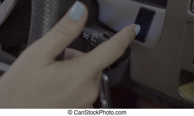 Woman driving car and using turn signal switch - Closeup...