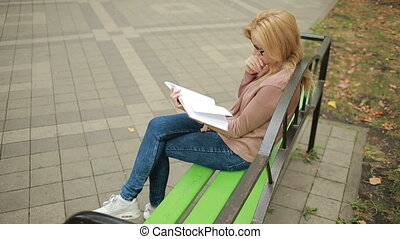 blonde Woman Reading Book on Brench in Autumn Park. - Woman...