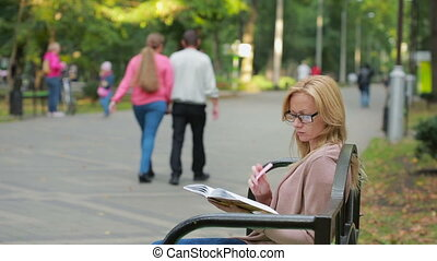 blonde Woman Reading Book on Bench in Autumn Park.