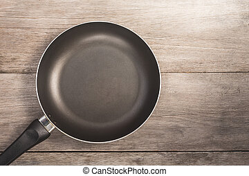 Top view teflon pan on wooden plank background
