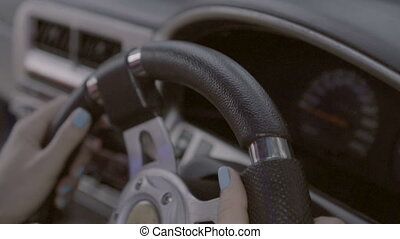 Closeup hands of female driver at the steering wheel -...