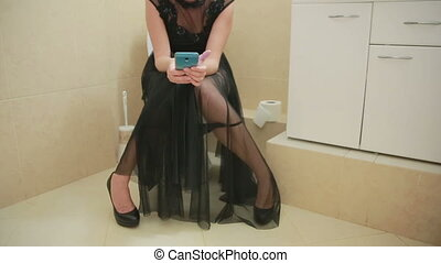 woman sitting on toilet in the bathroom. using smartphone. Evening Dress
