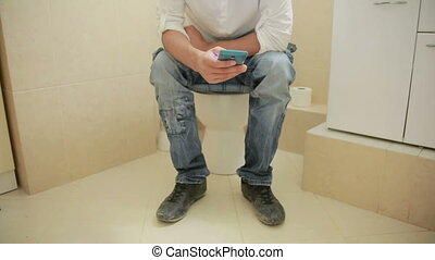 man sitting on a toilet and looks in the cell phone -...