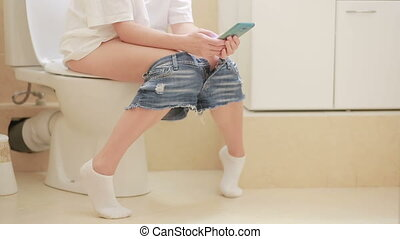 woman sitting on toilet in the bathroom. girl using her smartphone