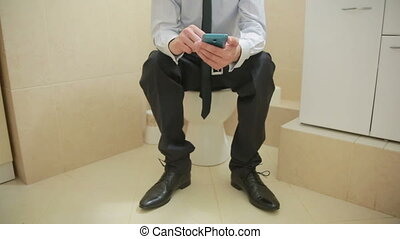 Male businessman watches the news on the phone sitting on...