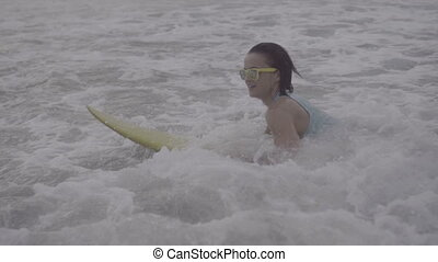 Beautiful woman with yellow surfboard on the beach - Side...
