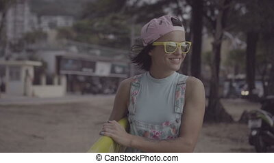 Happy woman in yellow sunglasses and pink hat walking with surfboard