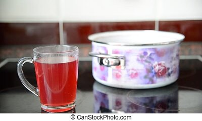 cup of hot compote and pan stand on the plate - A cup of hot...