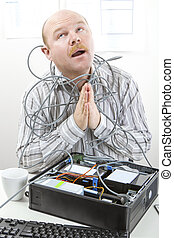 Businessman Tangled In Cables While Praying At Desk - Mature...
