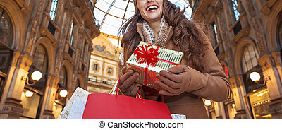 tourist woman with Christmas gift in Milan looking into...