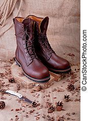Brown boots on wooden background near pine cone, sackcloth...