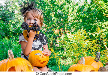 Halloween. Child dressed in black with jack-o-lantern in...