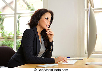 Successful business woman in office with computer
