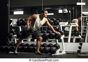 Hard working athletic man training with a dumbbell -...