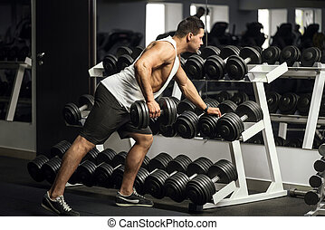 Well built strong man holding a dumbbell - Intensive...