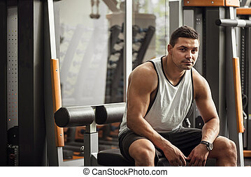 Good looking professional sportsman sitting in a gym -...