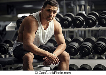 Athletic well built man sitting in a gym - Strong...